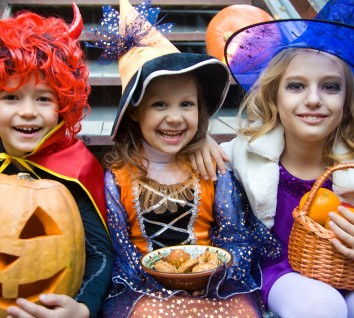 children in halloween costumes with pumpkin fooled on holiday